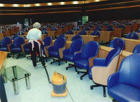 Schoonmaakster in vergaderzaal Tweede Kamer aan het stofzuigen